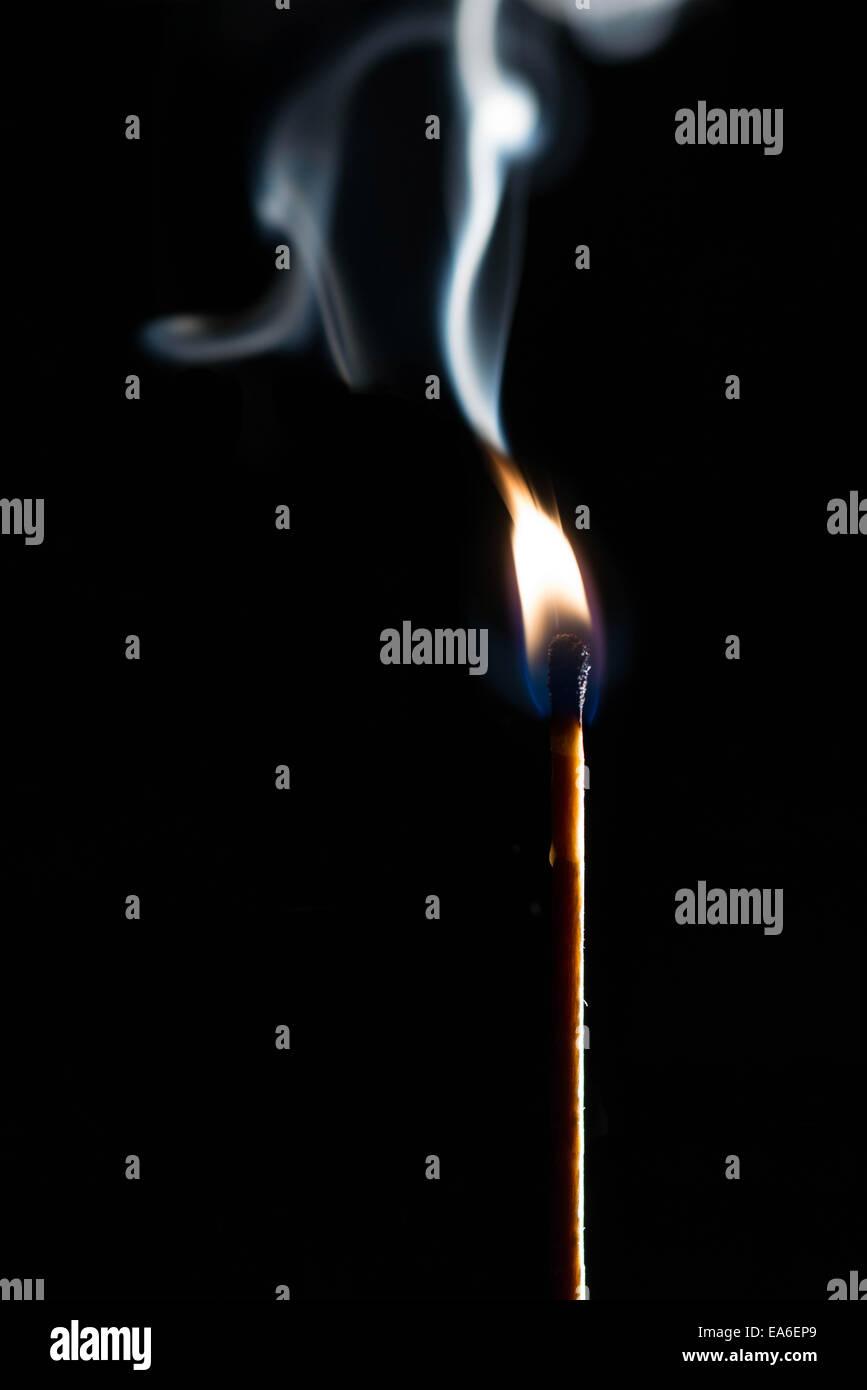 Match stick with smoke on black background - Stock Image