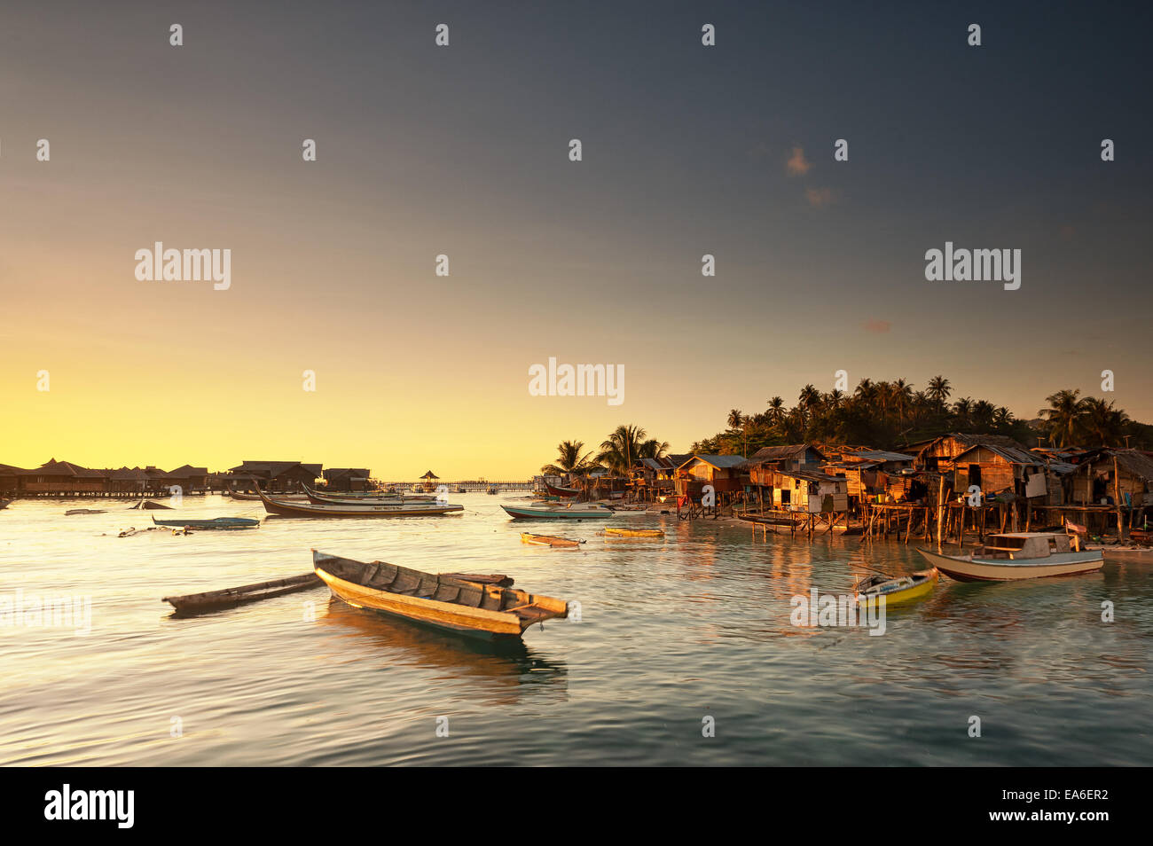 Malaysia, Sabah, Small boats and Sea Gypsy huts at sunrise - Stock Image