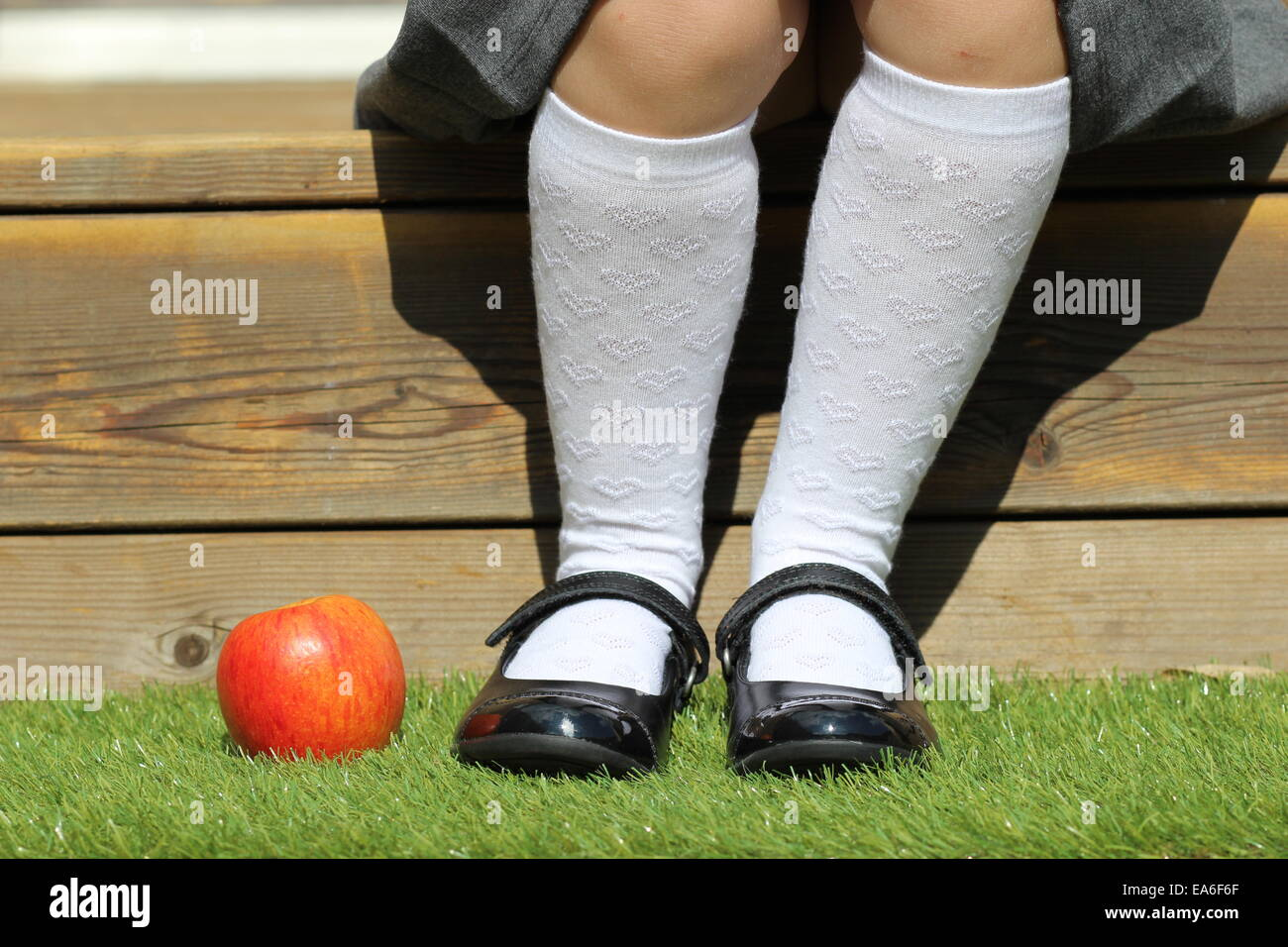 Girl sitting on step with apple on grass by her feet - Stock Image