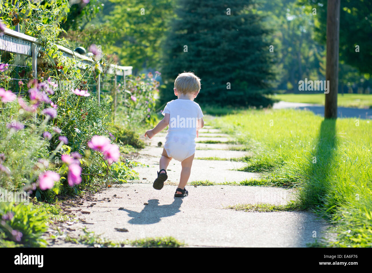 Boy running along sidewalk, Indiana, America, USA - Stock Image