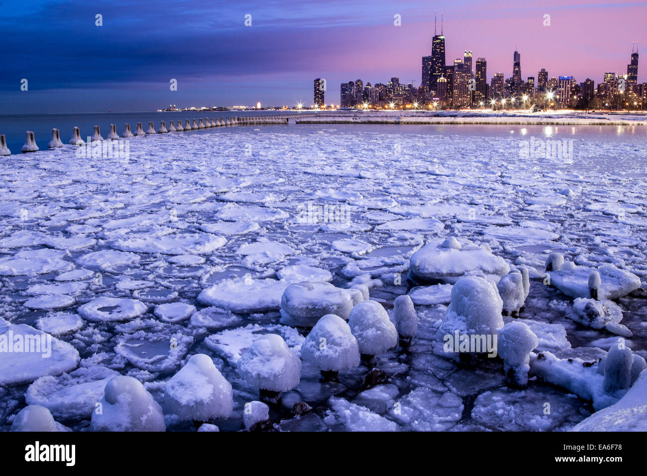 USA, Illinois, Chicago, Illuminated skyline seen across icy harbor - Stock Image