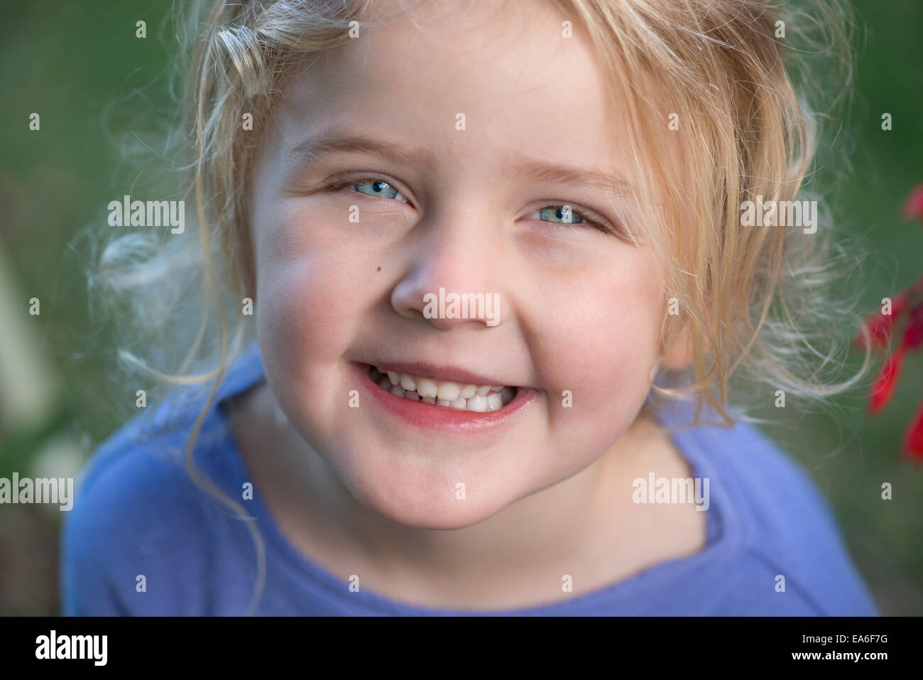 Blonde girl (4-5) in purple jumper smiling - Stock Image