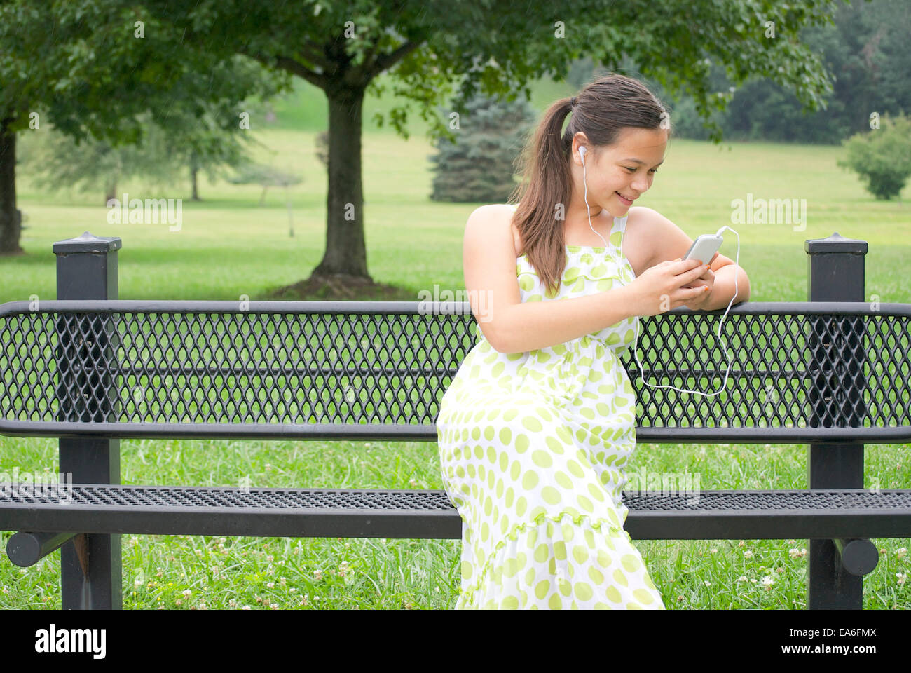 Girl (10-11 years) on bench with smartphone - Stock Image