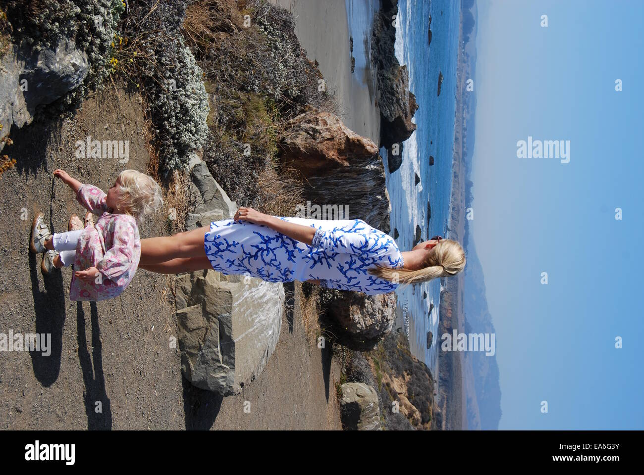 Mother and daughter standing on beach looking at sea view - Stock Image
