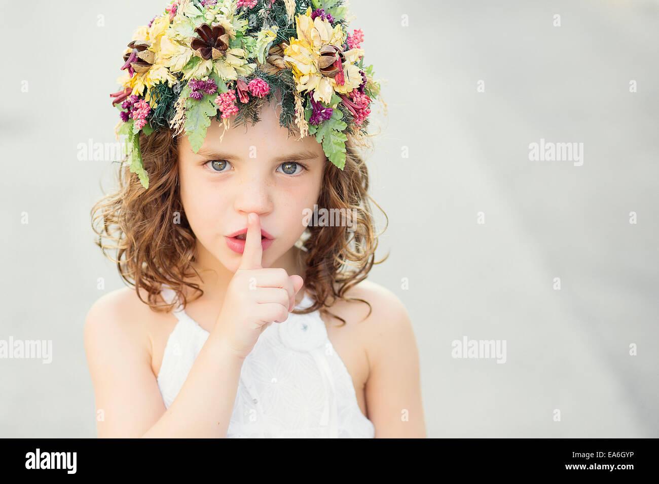 Girl shushing with finger on her lips - Stock Image