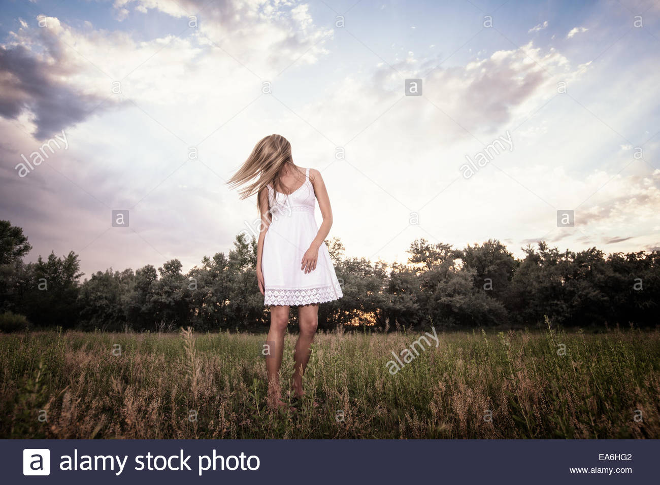Woman standing in a meadow - Stock Image