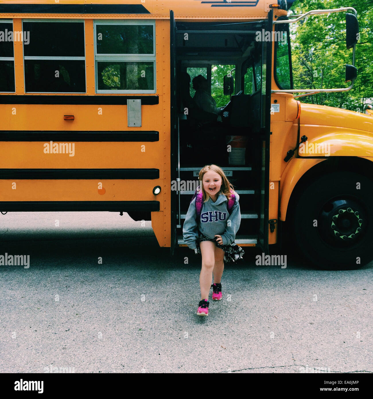 Smiling Girl getting off school bus, Wisconsin, America, USA - Stock Image