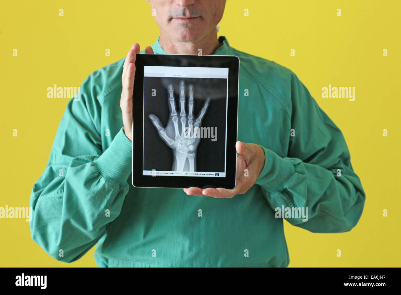 Surgeon holding tablet showing x-ray - Stock Image