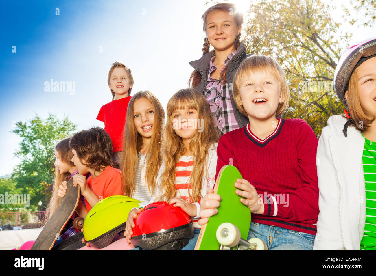 Positive children with skateboards and helmets - Stock Image