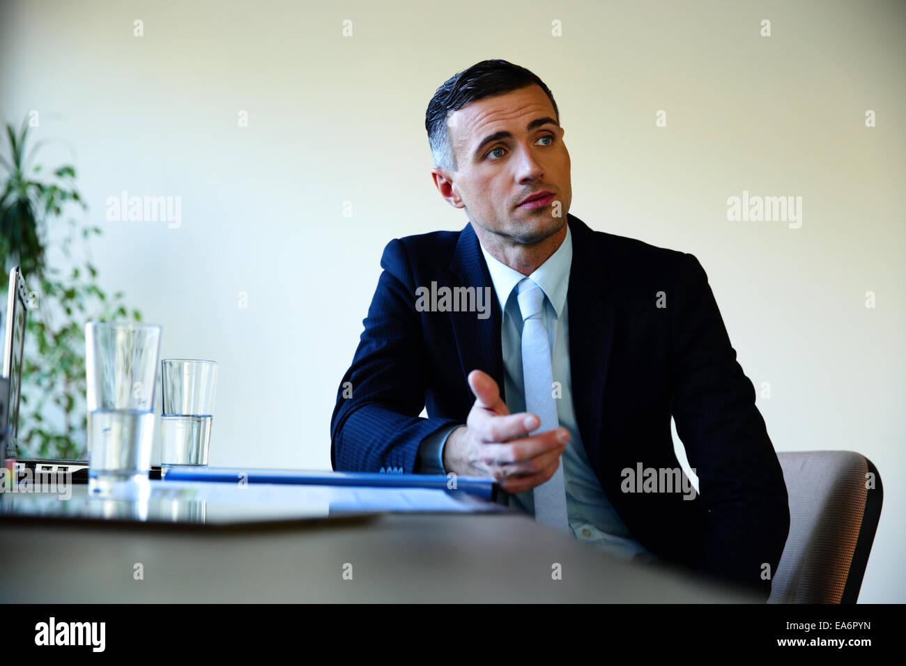 Businessman sitting at the table and explaining something - Stock Image