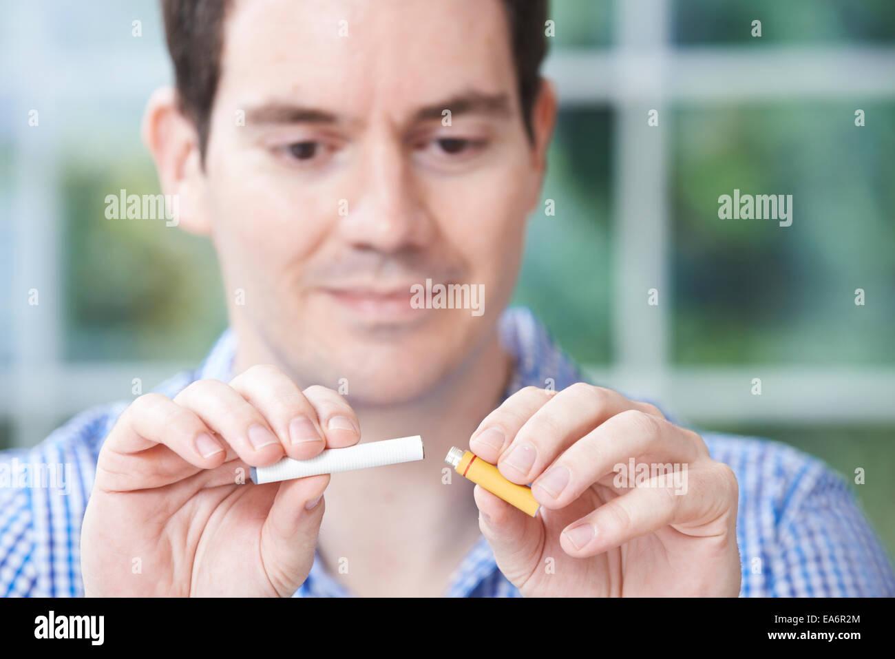 Man Using Electronic Cigarette To Stop Smoking - Stock Image
