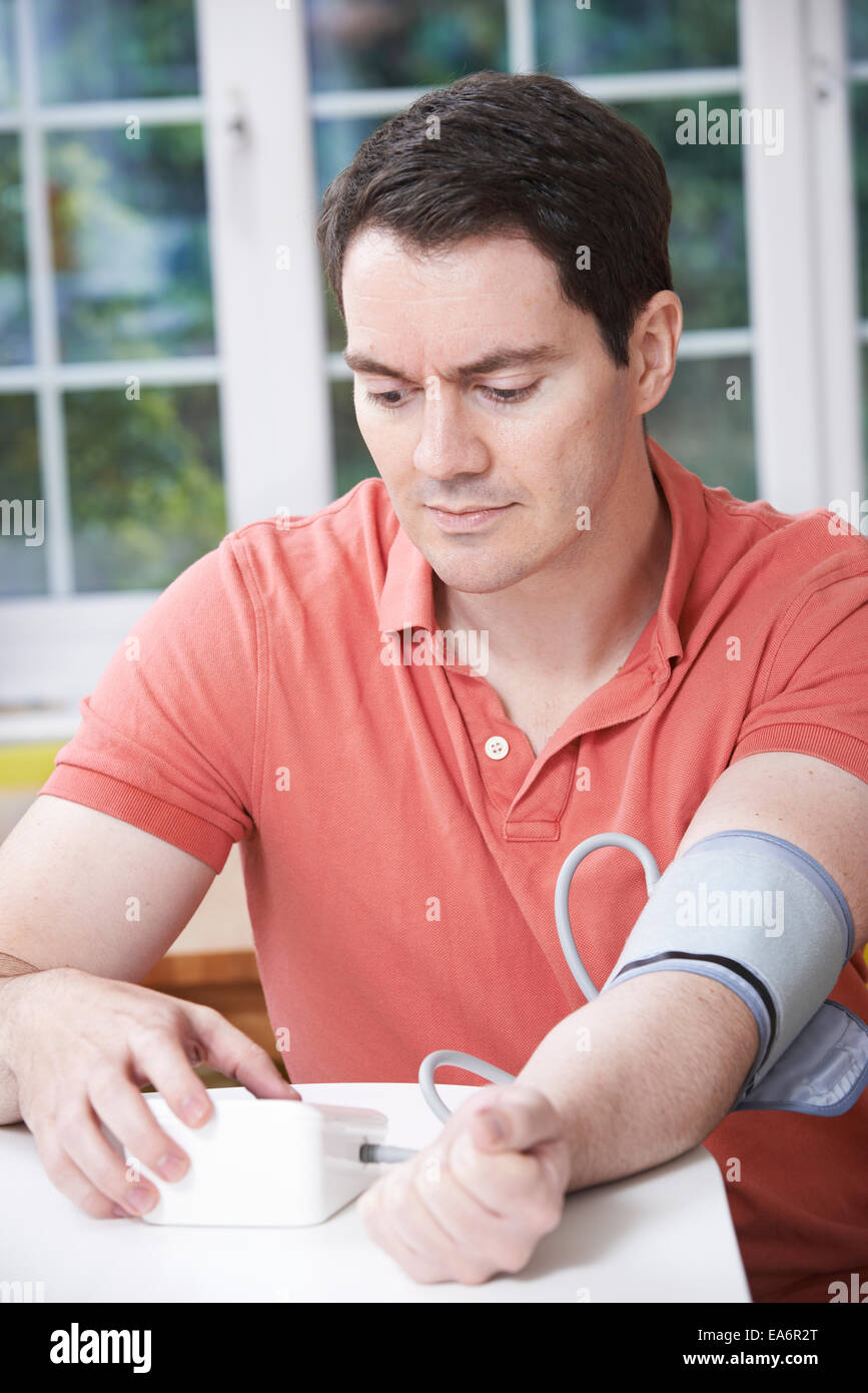 Man Measuring Blood Pressure At Home - Stock Image