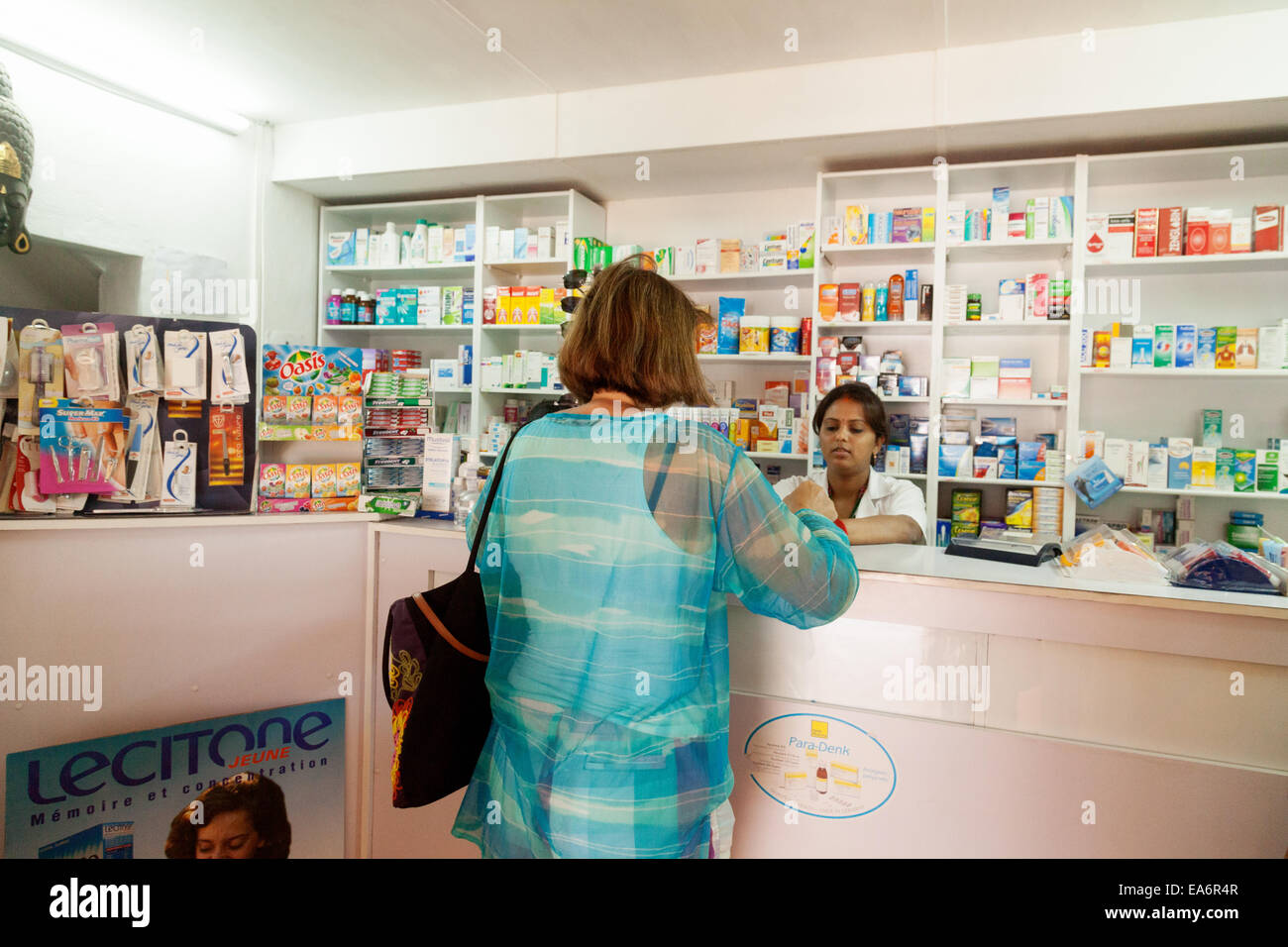 A woman shopping in a chemist pharmacy, Belle Mare village, Mauritius - Stock Image