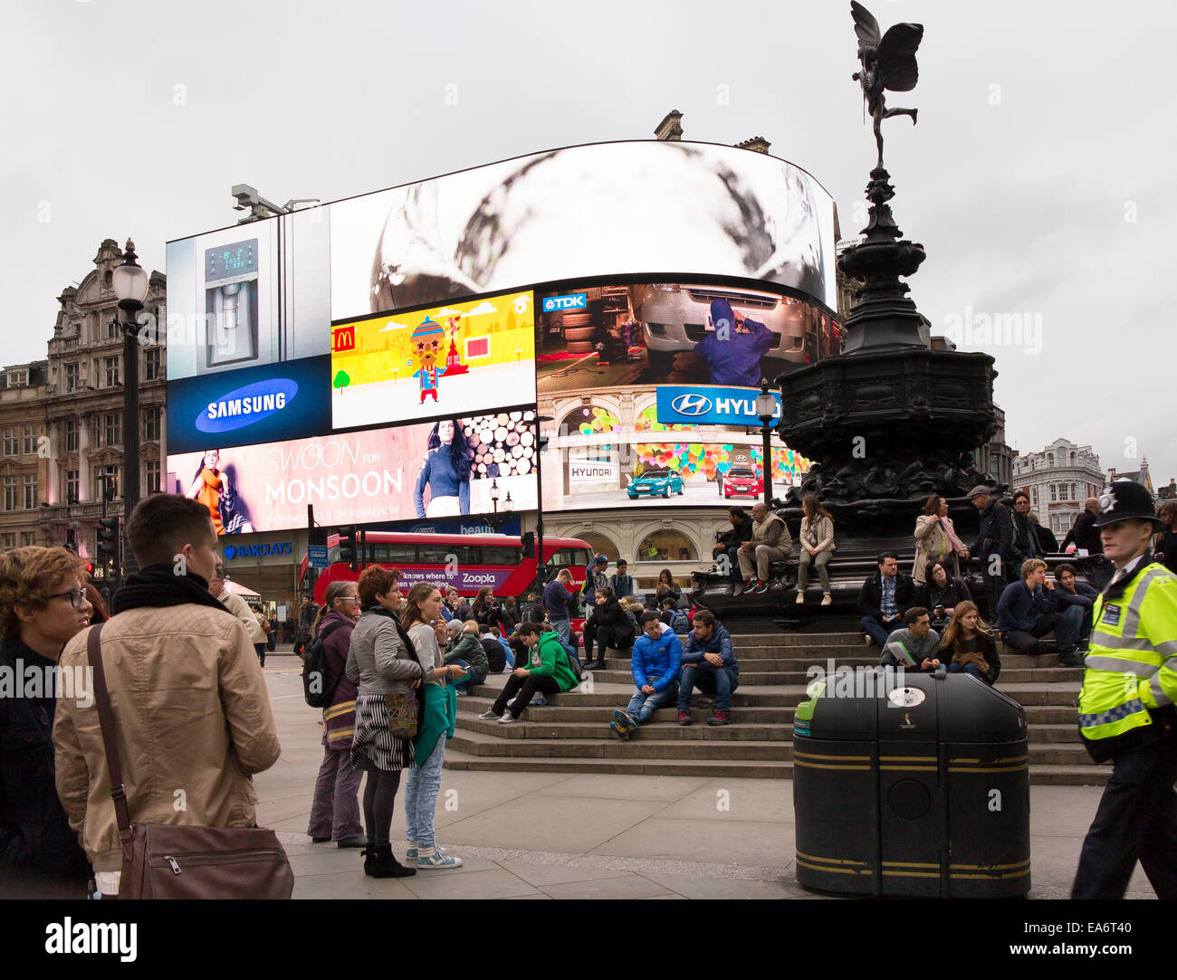 Tourists and a single police officer at Piccadilly Circus London - Stock Image