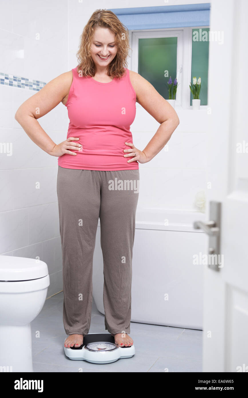 Happy Woman Weighing Herself On Scales In Bathroom - Stock Image