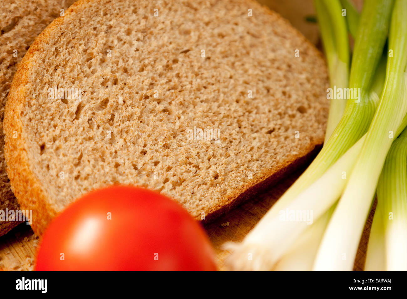 wholemeal (wholewheat) bloomer bread slices presented with spring onions and a tomato - Stock Image