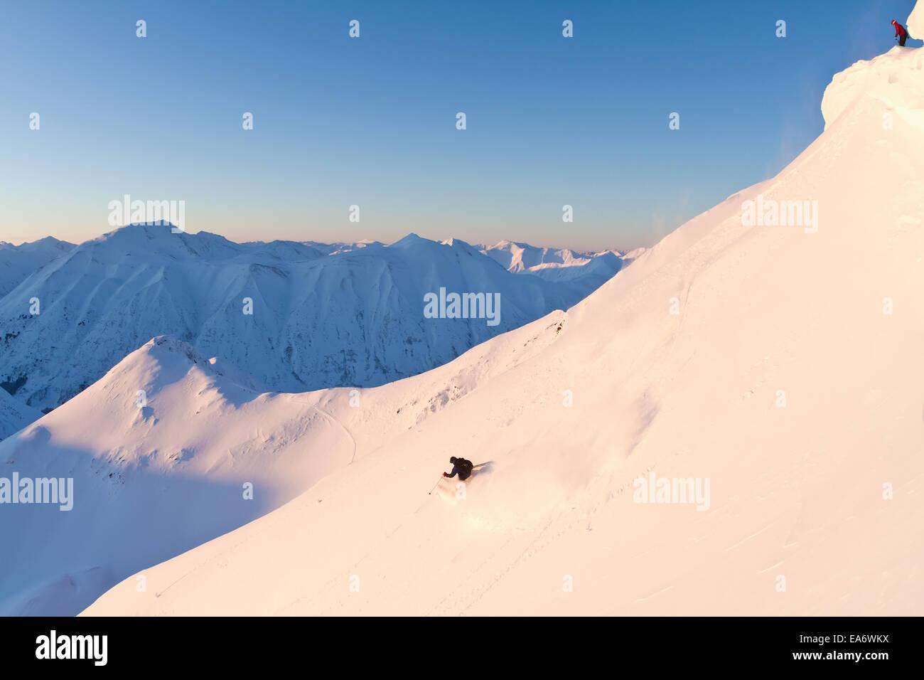 A skier watching another skier from above at Turnagain Pass, Kenai Mountains, Southcentral Alaska; Alaska, USA - Stock Image