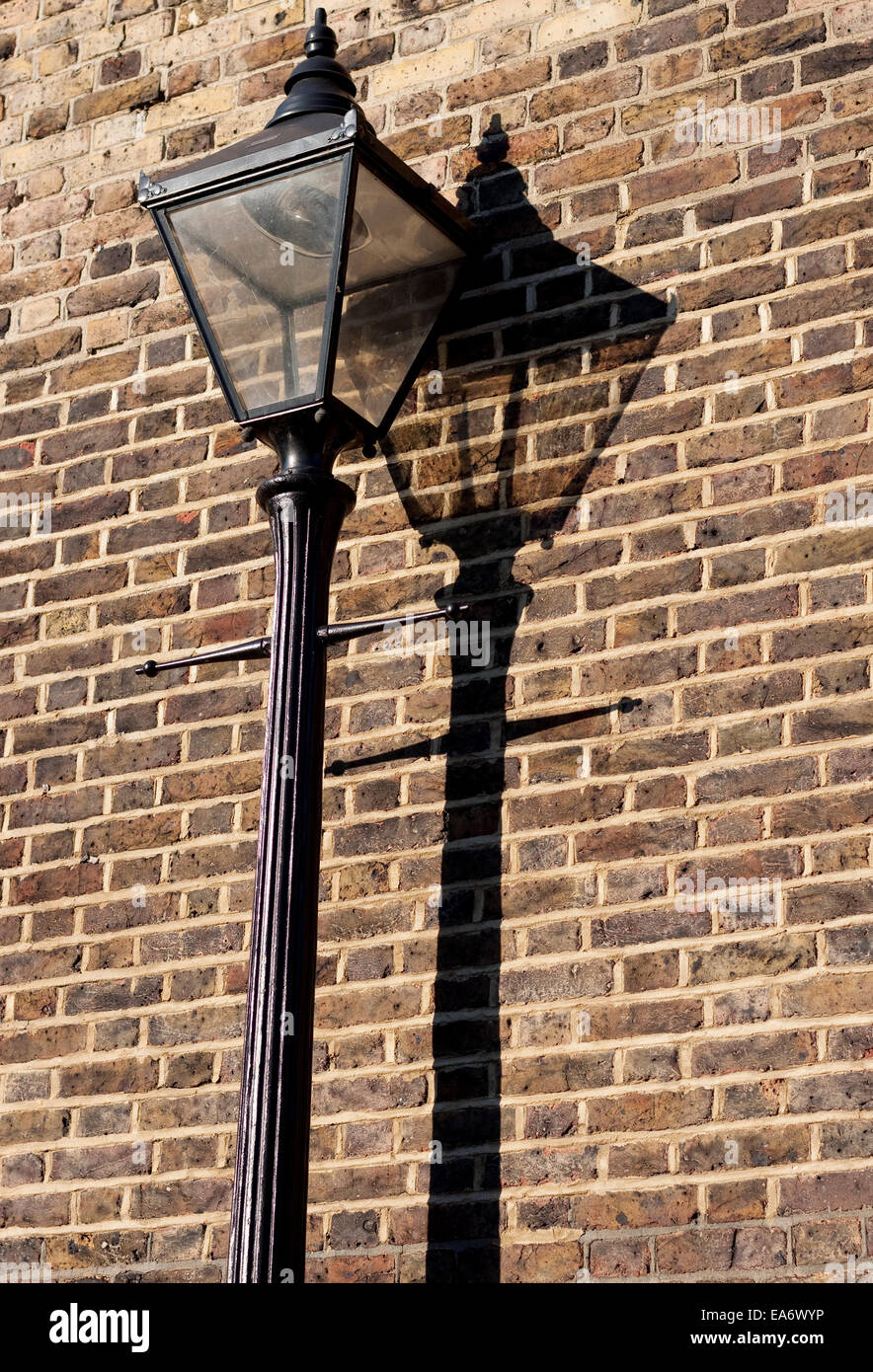 A gas street light in London casts a shadow on a brick wall - Stock Image