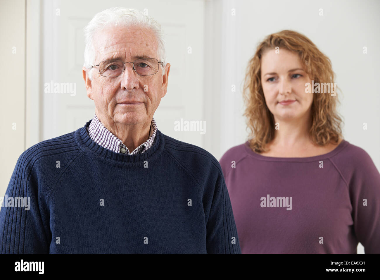 Serious Senior Man With Adult Daughter At Home - Stock Image