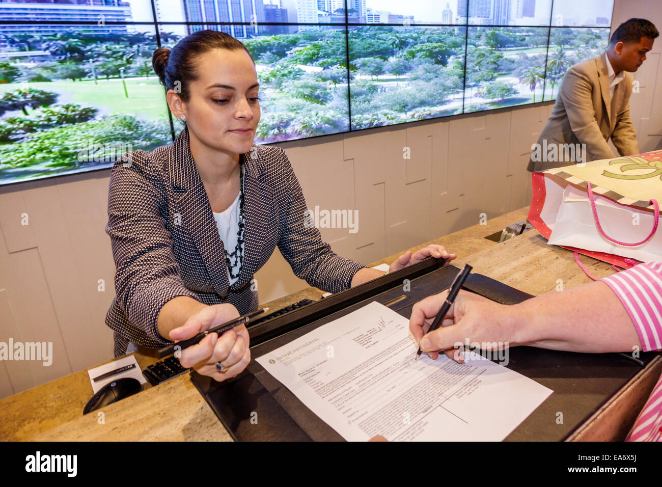 Miami Florida Intercontinental hotel lobby front desk reservations woman employee working job - Stock Image
