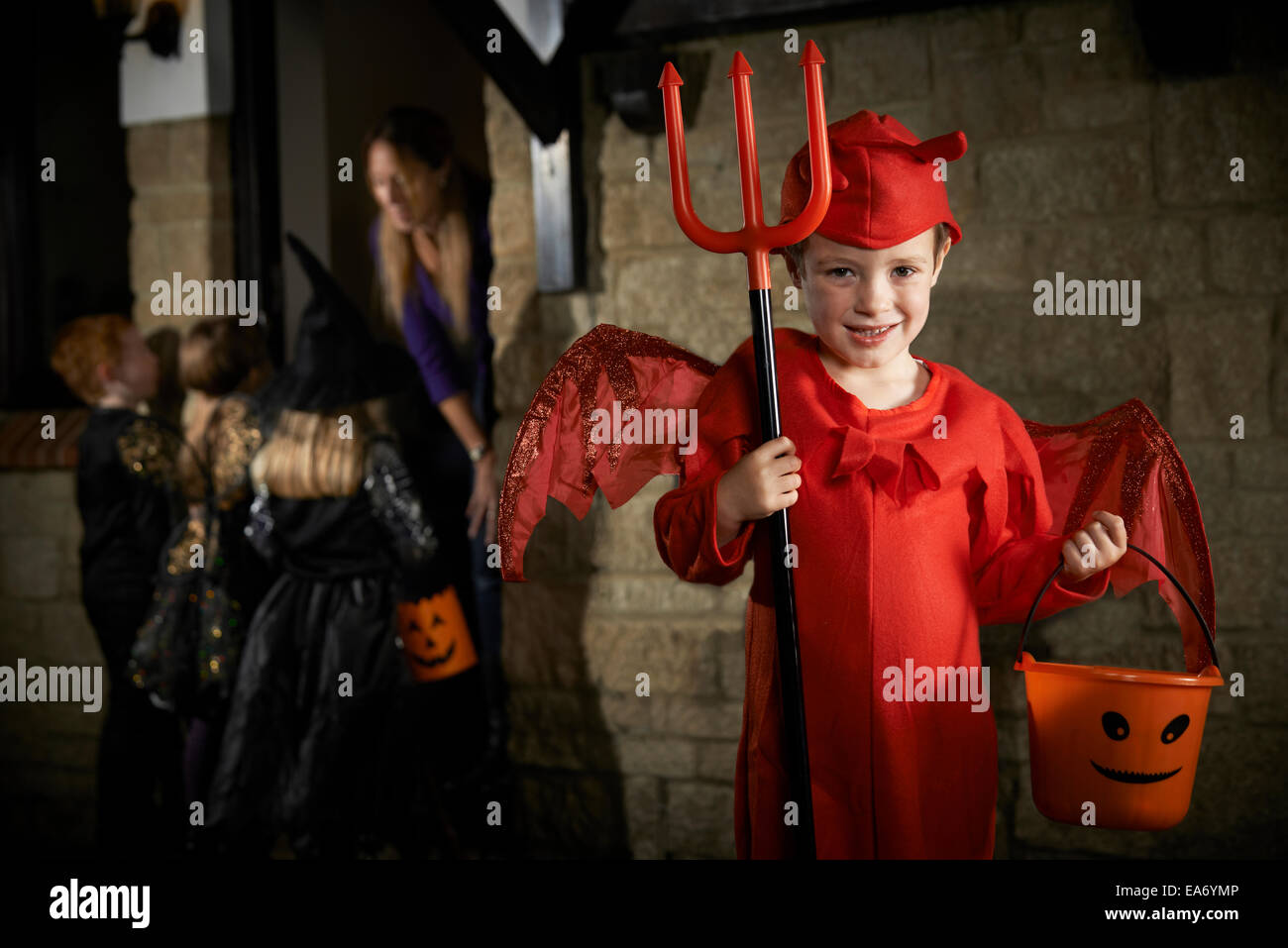 Halloween Party With Children Trick Or Treating In Costume - Stock Image