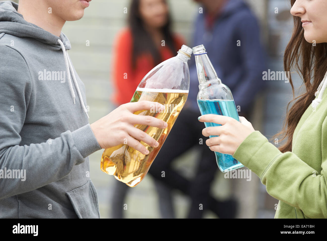 Close Up Of Teenage Group Drinking Alcohol Together - Stock Image