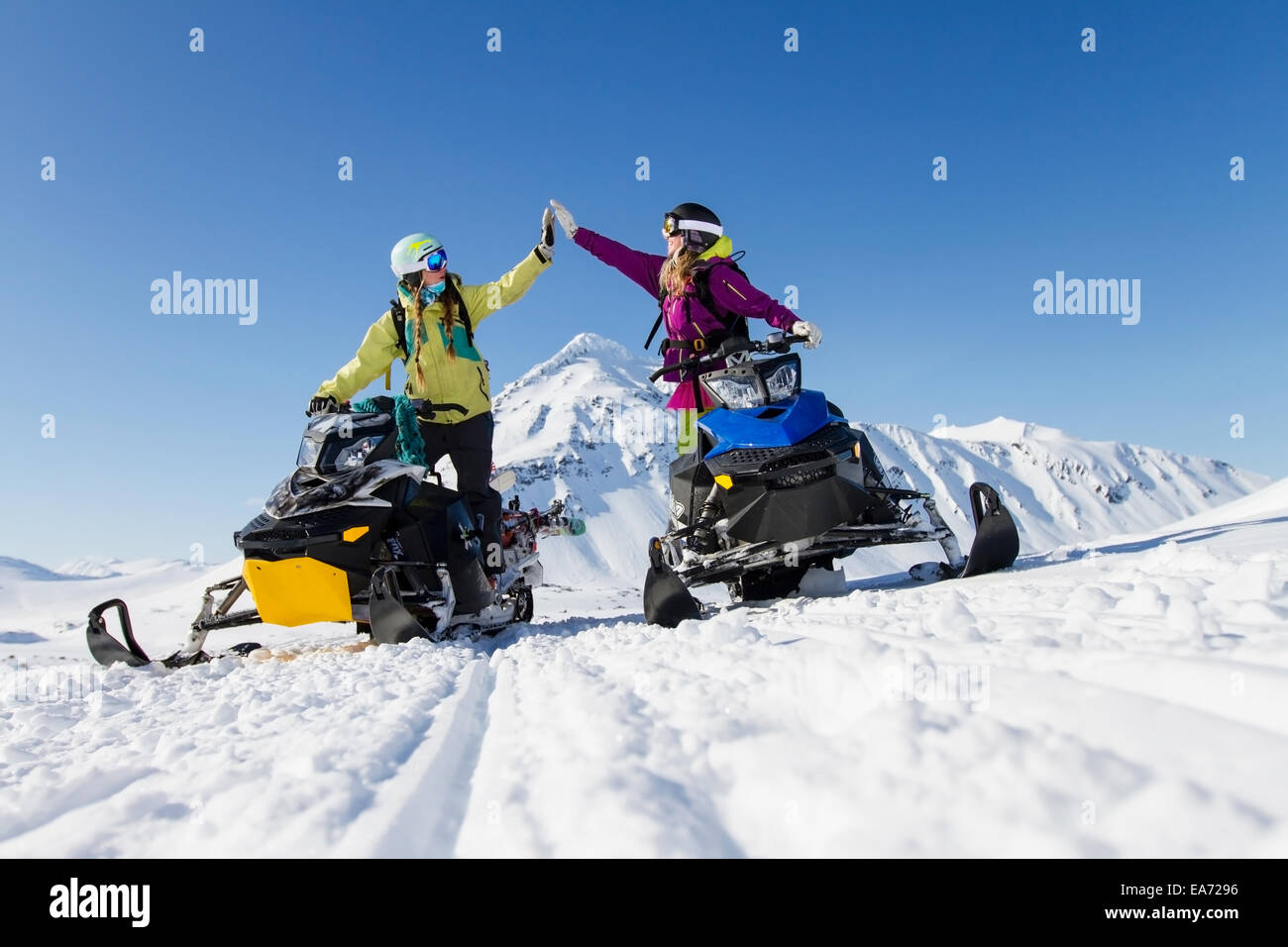 Women,Snowmobile,Alaska,Snow,Mountain,Hi-Five - Stock Image