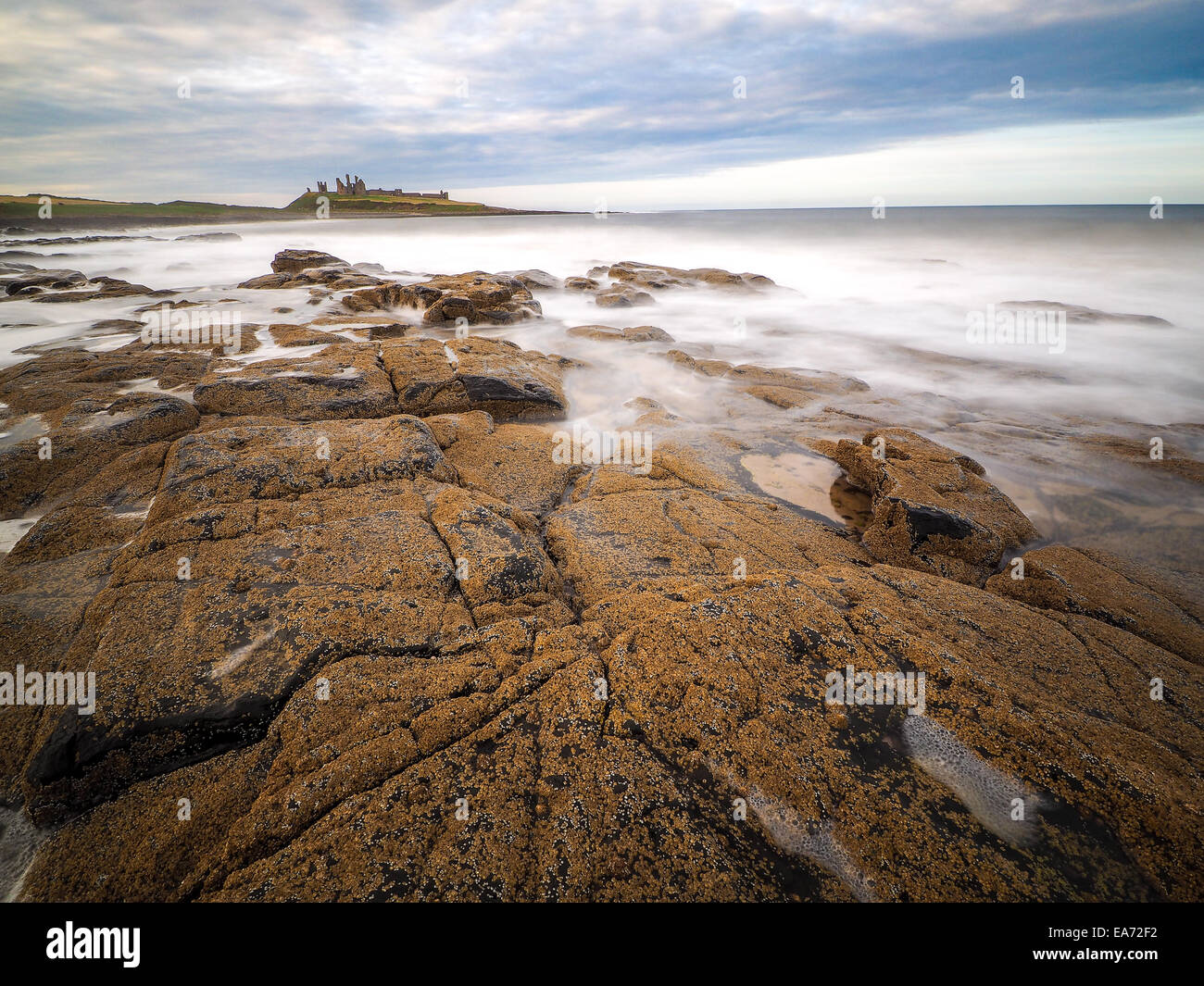 The stunningly rugged coastline of Holy Island in Northumberland is protected by Lindisfarne Castle on a beautiful Stock Photo