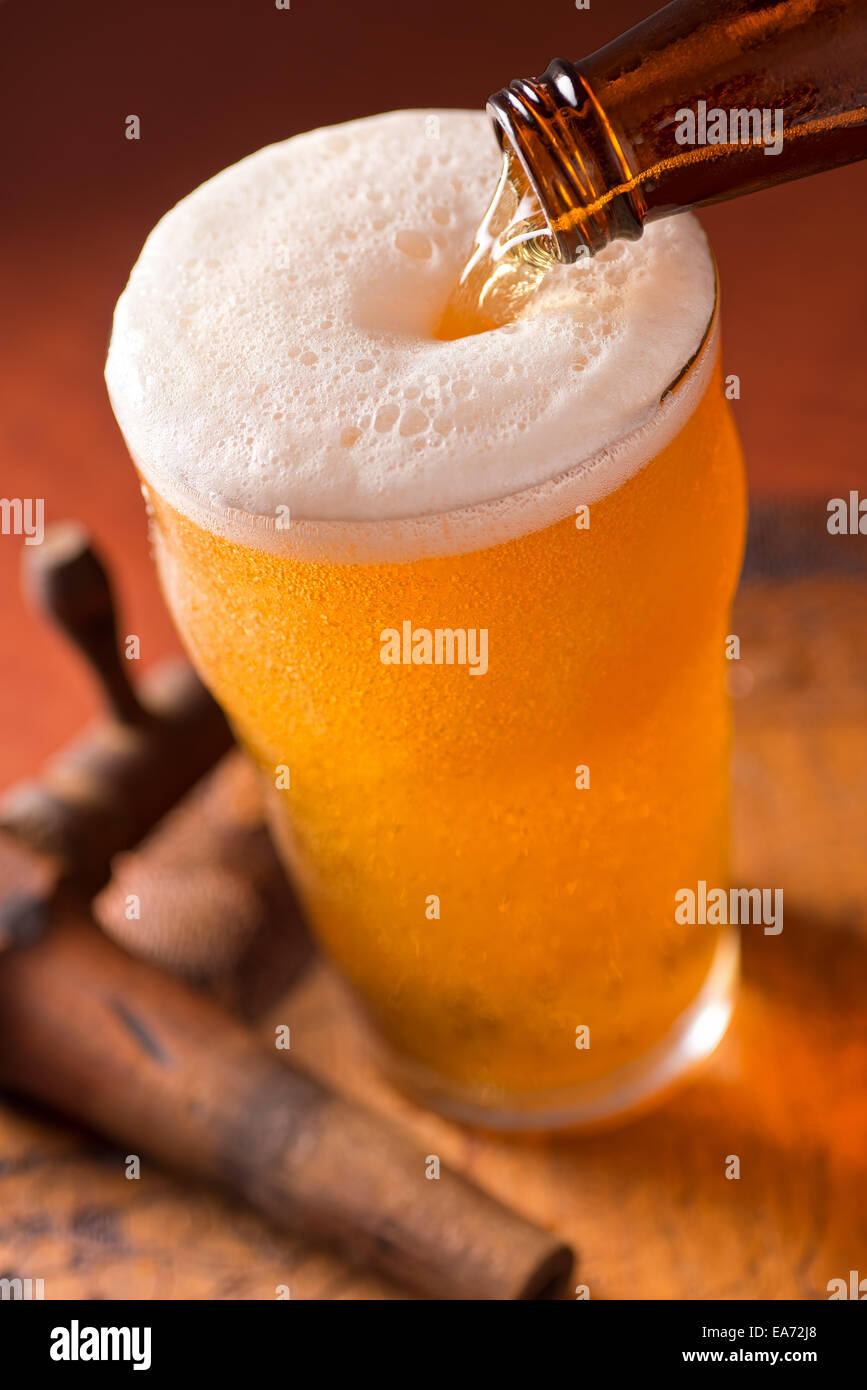 A glass of cold beer being poured on top of a rustic keg with antique spigot. - Stock Image