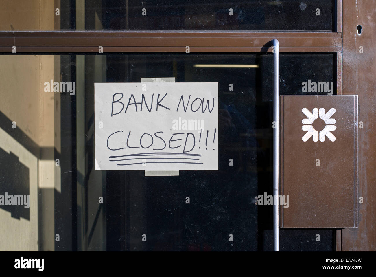 The door of a branch of the Royal Bank of Scotland (RBS) with a handwritten sign reading, 'Bank Now Closed'. - Stock Image