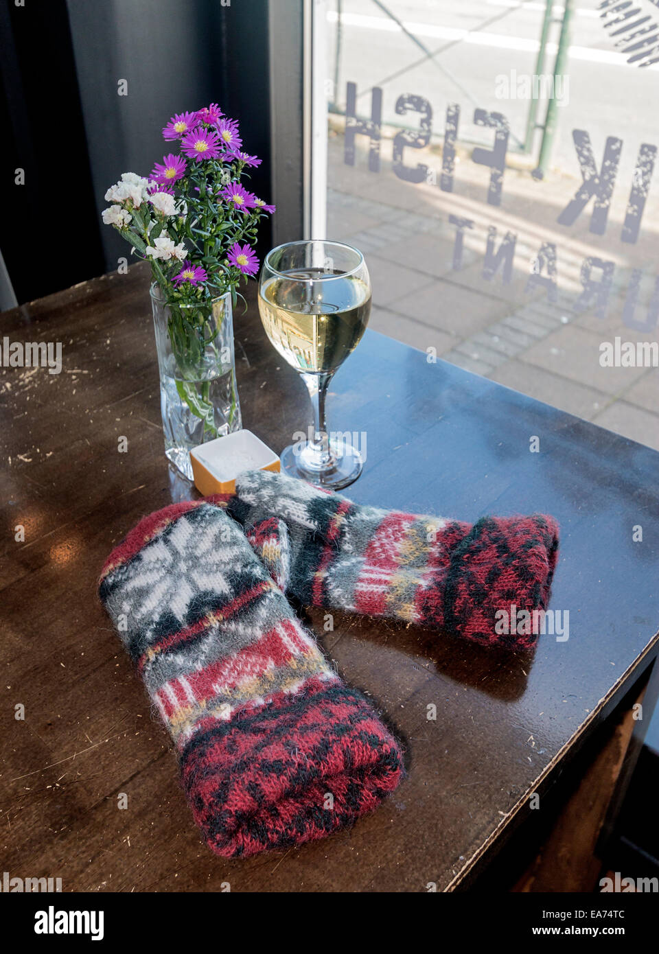 Wool Icelandic mittens, a glass of wine and flowers in a local restaurant in Reykjavik, Iceland. - Stock Image