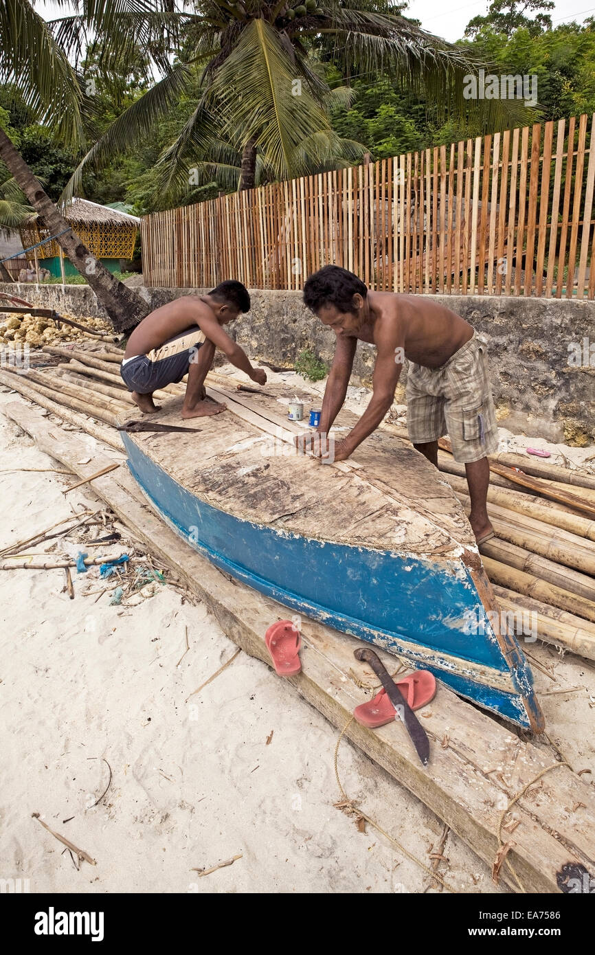 Two Filipino men repair the bottom of their fishing boat. - Stock Image