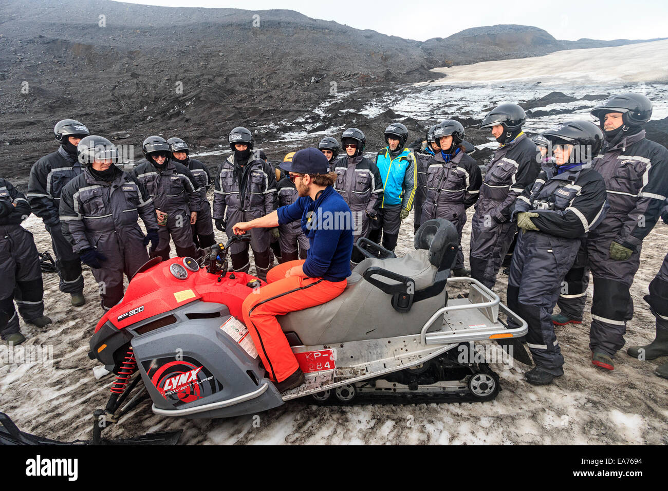 Guide instructs snowmobilers on Mýrdalsjökull, a glacier in the south of Iceland. - Stock Image