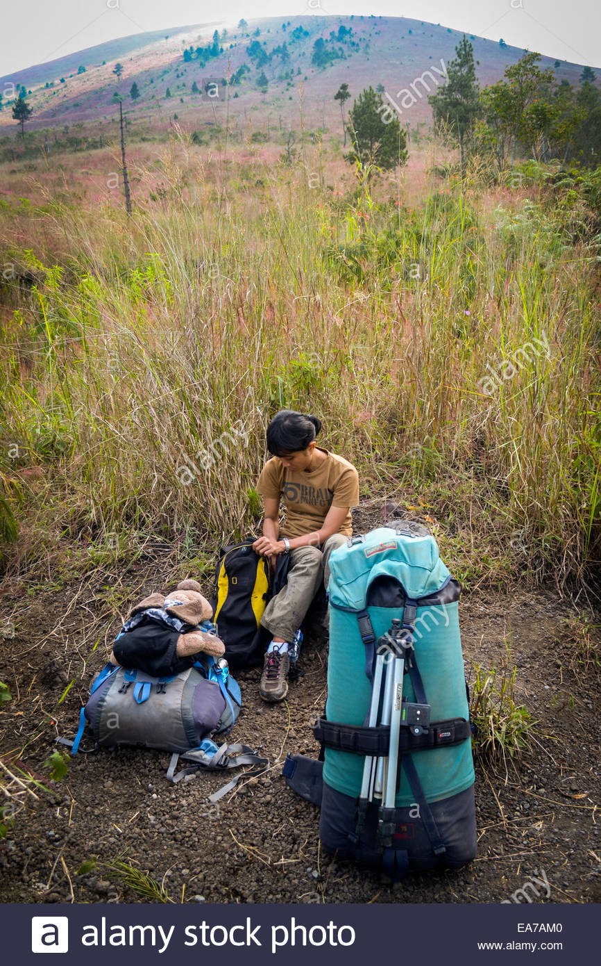A woman and her puppy doll take a rest during Mount Guntur climbing in West Java. © Reynold Sumayku Stock Photo