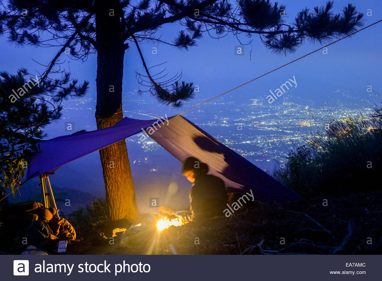 A woman below flying camp on the slope of Mount Guntur in West Java, Indonesia. - Stock Image