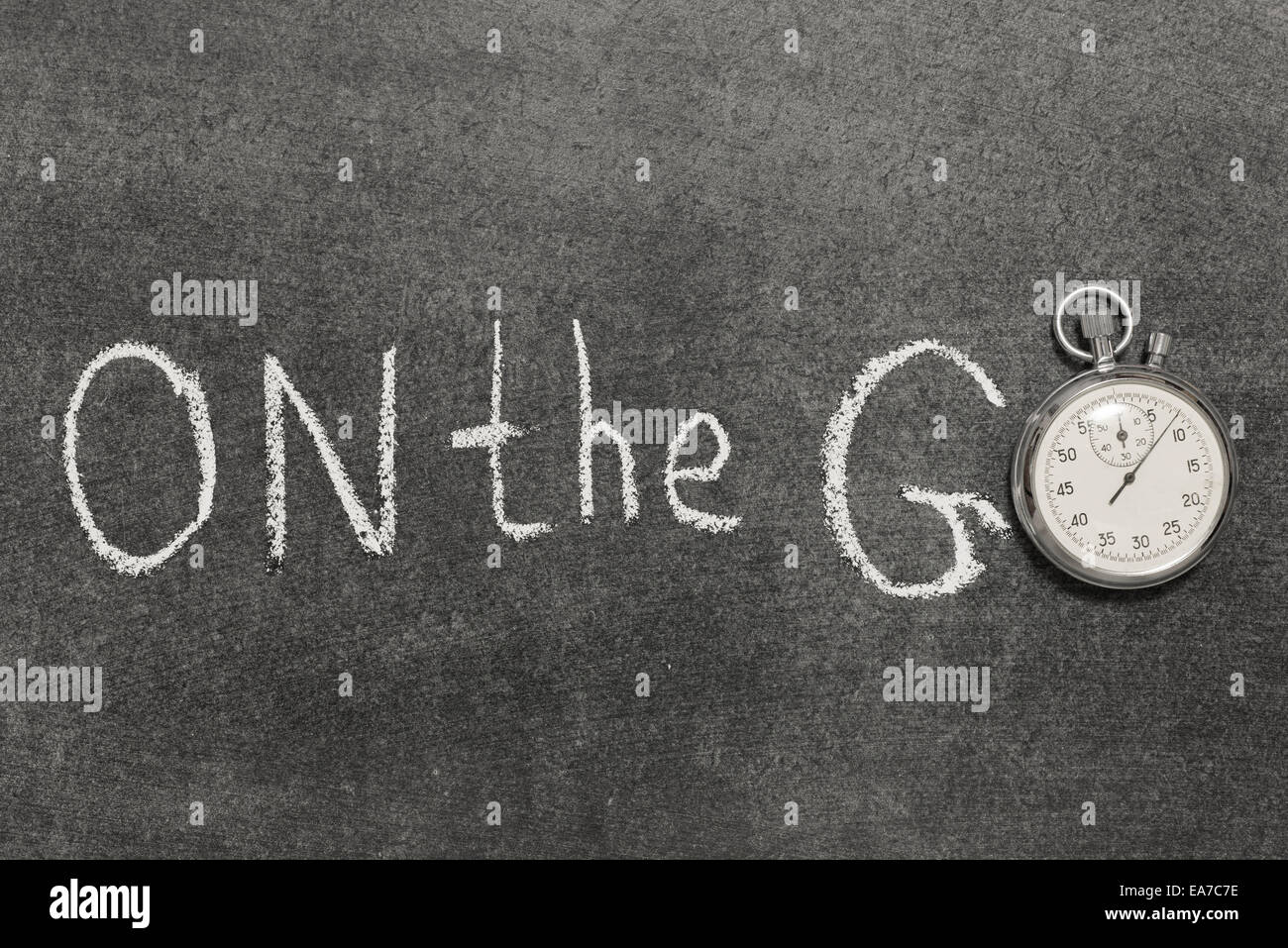 on the go phrase handwritten on chalkboard with vintage precise stopwatch used instead of O - Stock Image