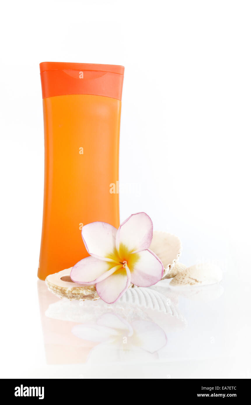 Bottle of sunblock with flower and shells on white background - Stock Image