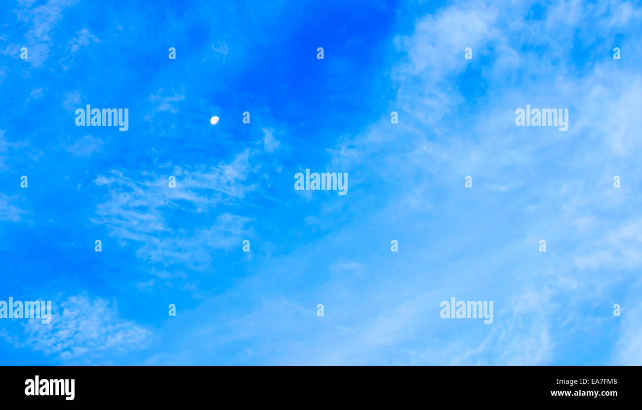 The Moon and Bright Cloudy Blue Sky. - Stock Image