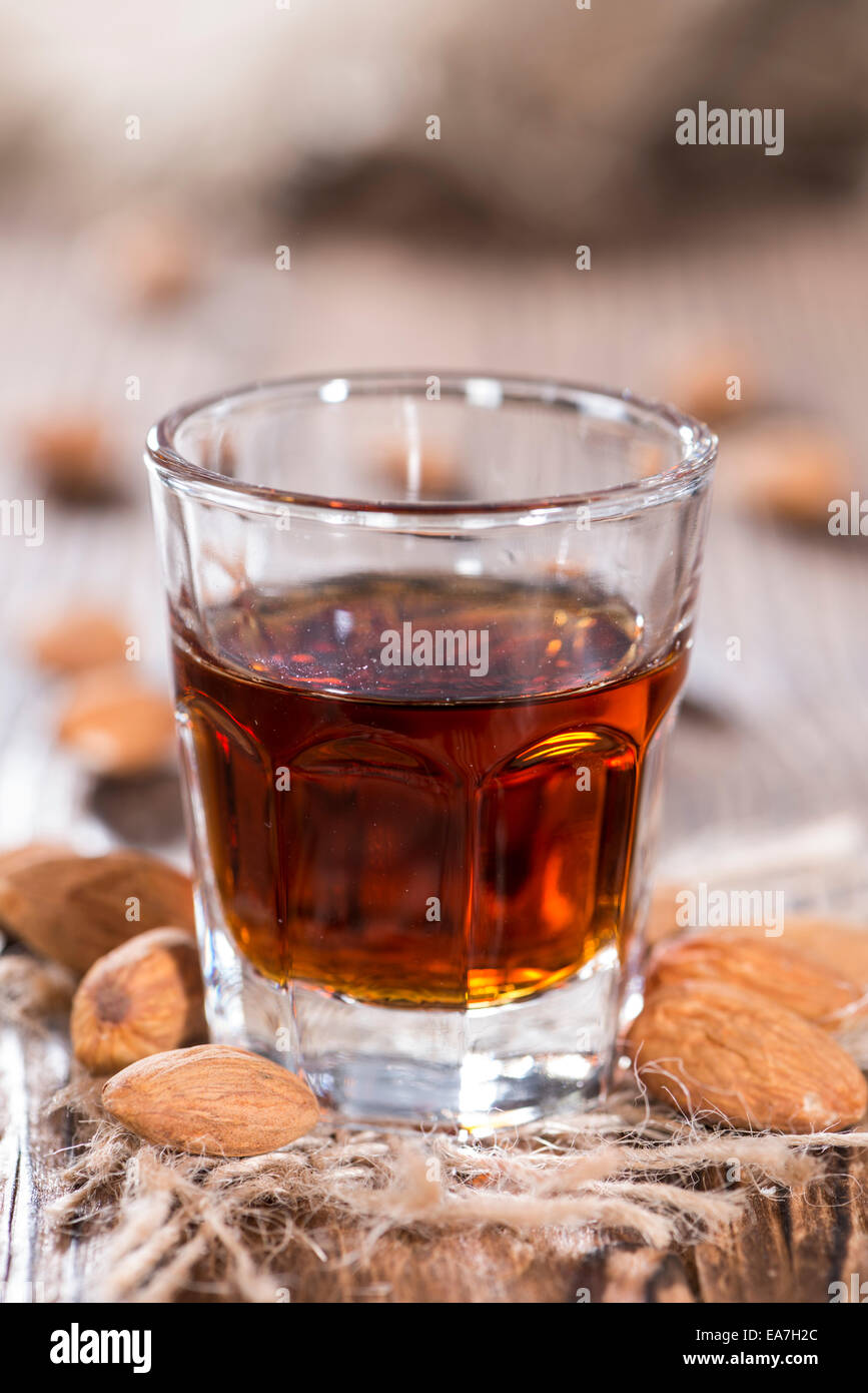 Amaretto Shot on dark wooden background with some almonds - Stock Image