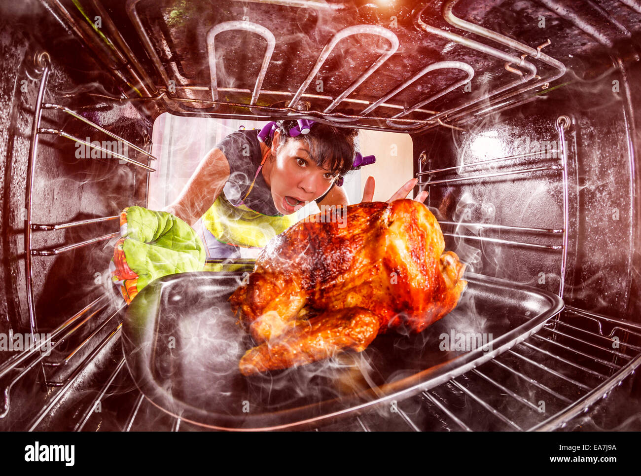 Funny Housewife overlooked roast chicken in the oven, so she had scorched , view from the inside of the oven. Housewife - Stock Image