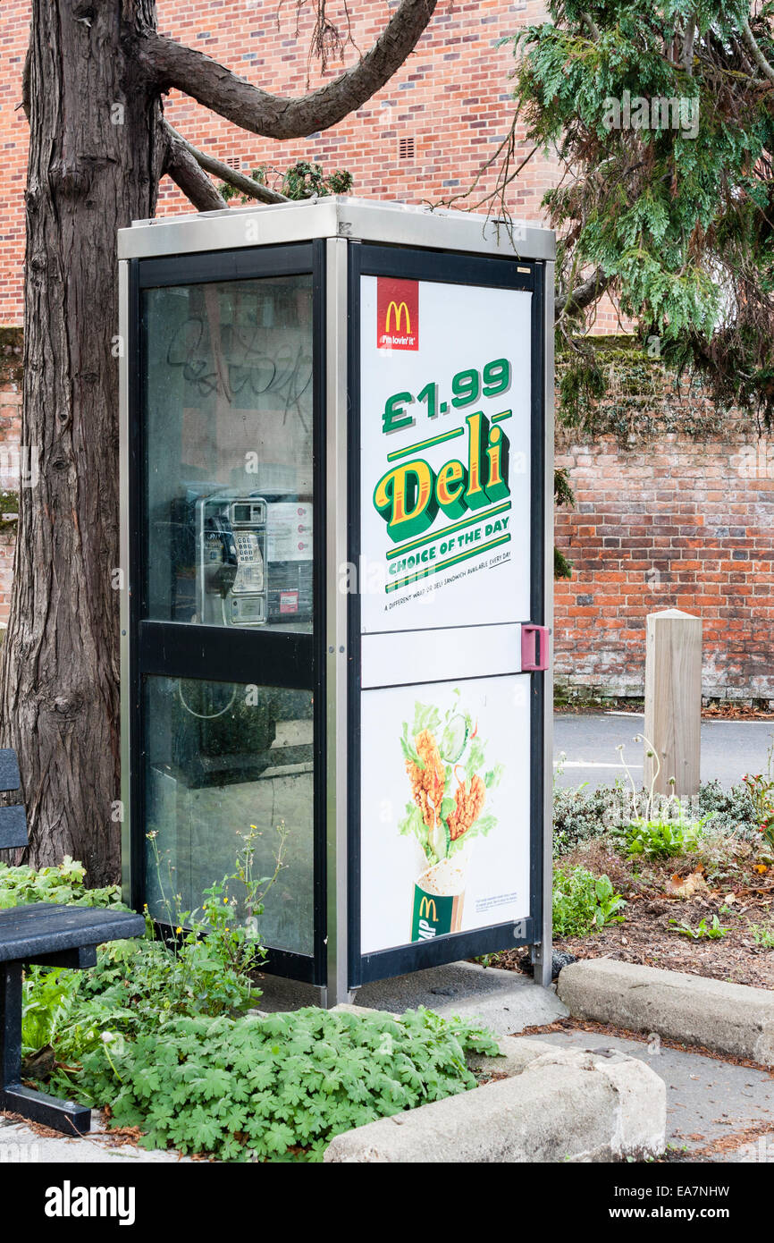 BT public phone booth with advertising on the glass for McDonalds products. Maidenhead, Berkshire, England, GB, - Stock Image