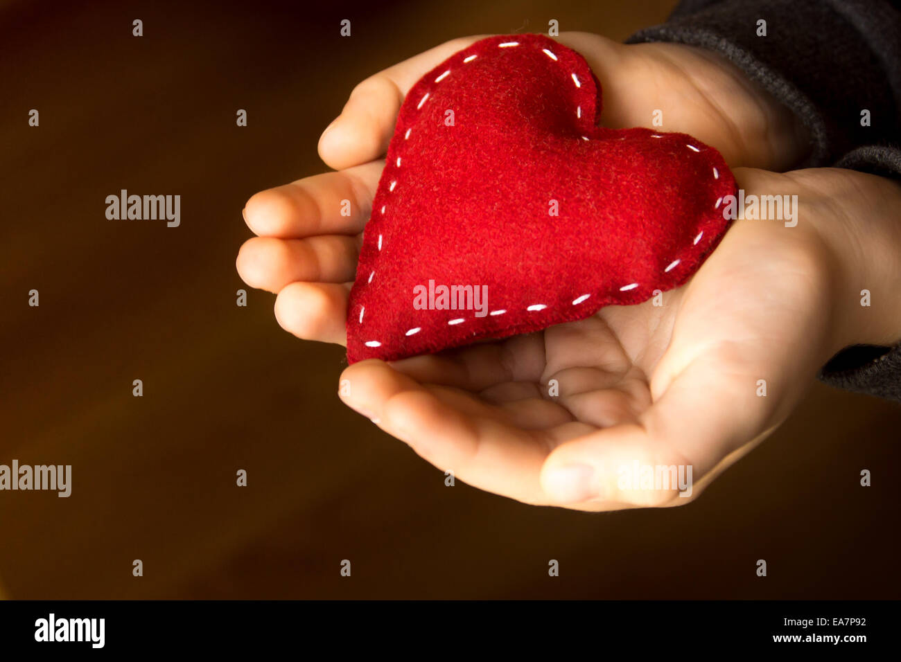 Red heart in child hands, hand made gift, valentine day and family love concept, close up, horizontal - Stock Image