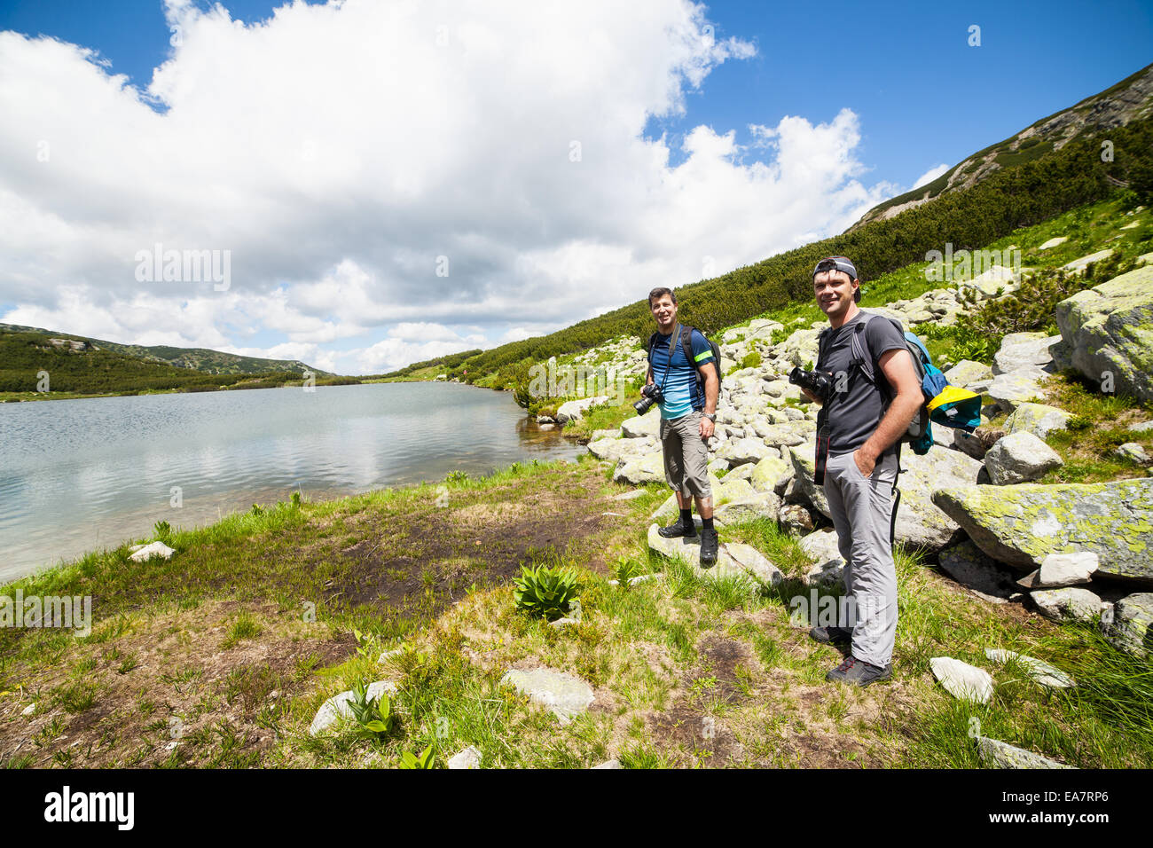 Two caucasian hikers with backpacks walking around a lake in the mountains Stock Photo