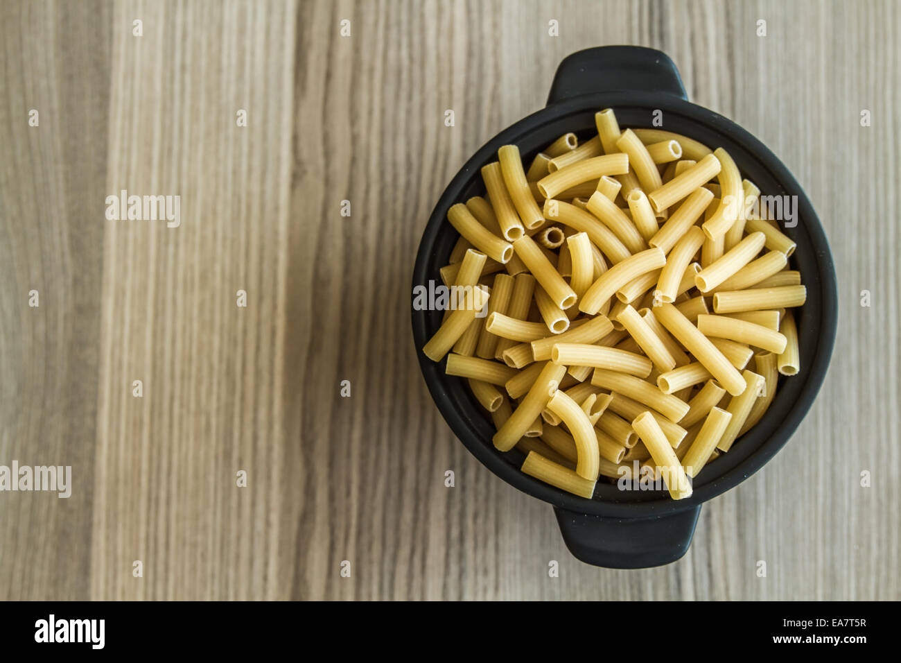Italian dry pasta in a black Bow on a wooden table Stock Photo