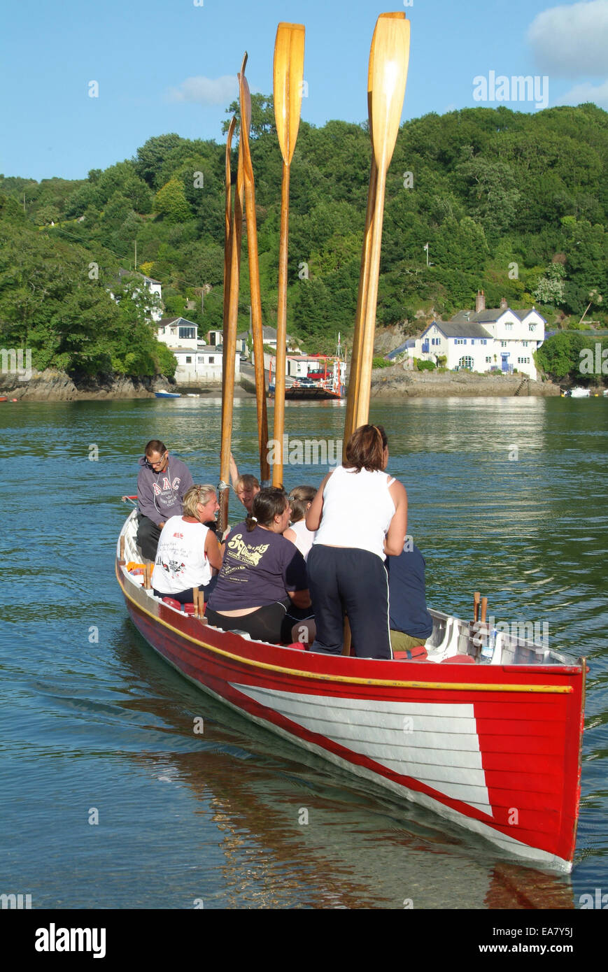 Gig with rowers holding oars upright on the River Fowey opposite Bodinnick landing at Fowey Restormel Mid Cornwall - Stock Image
