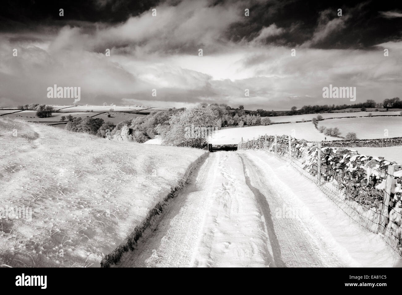Country track with views across valley to distant hills near brassington in the Peak District Derbyshire UK winter. - Stock Image