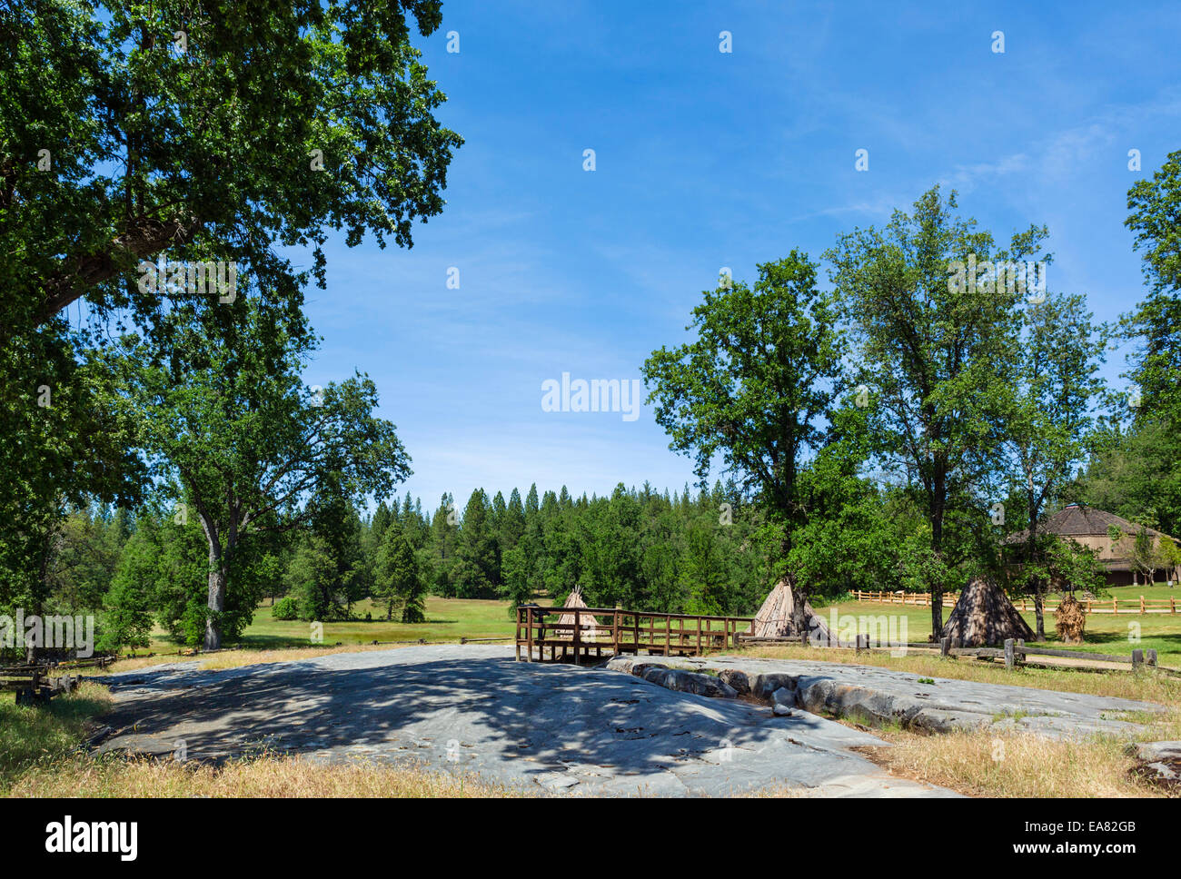 The grinding rock with Miwok bark homes behind, Indian Grinding Rock State Historic Park, Southern Gold Country, - Stock Image