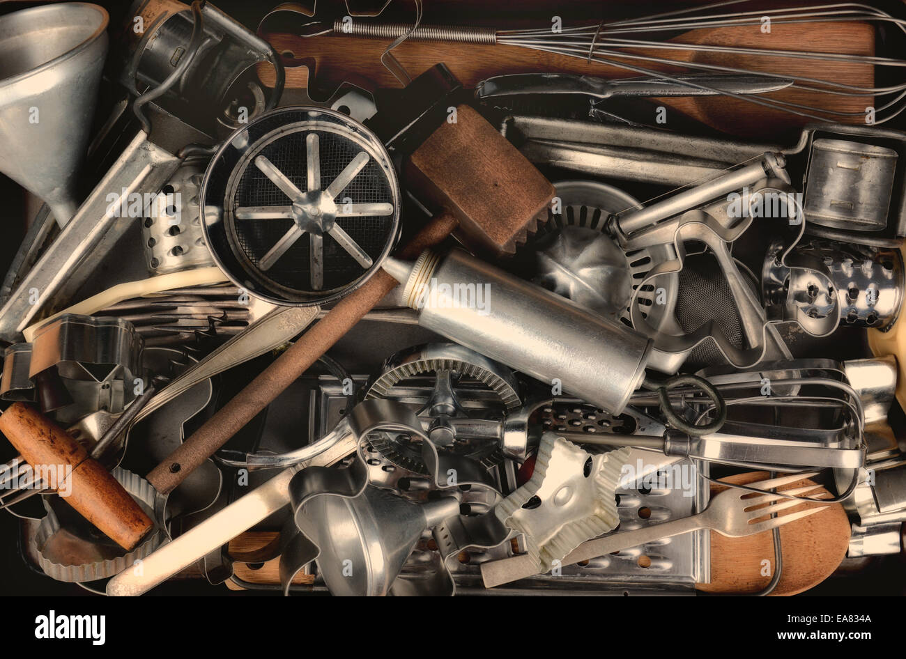 Closeup of a group of old metal and wood kitchen utensils. Items include: sifter, funnel, cookie cutters, forks, - Stock Image