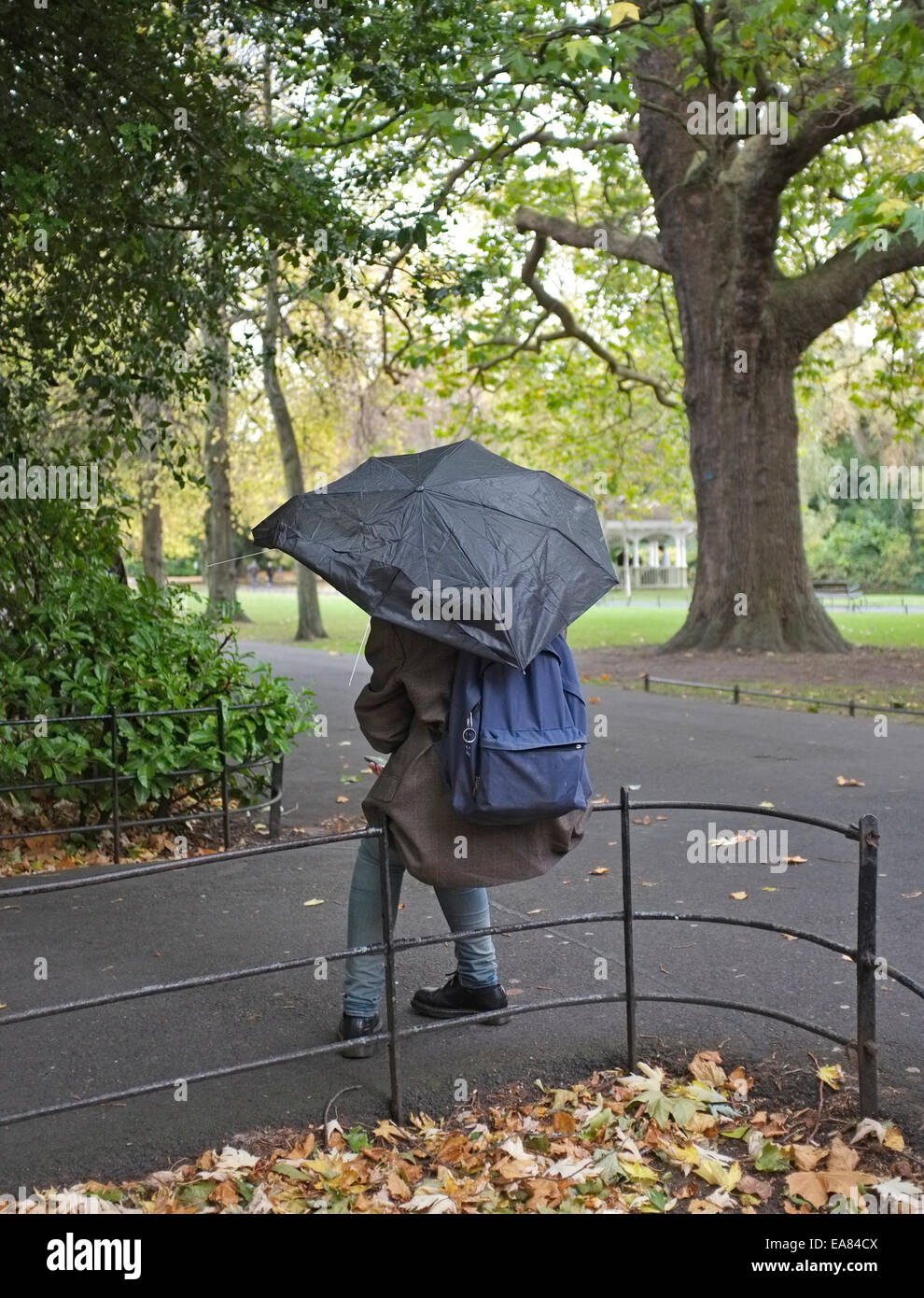 c2bf19d5addc a girl sits on a rail with broken umbrella in st. stephens green ...