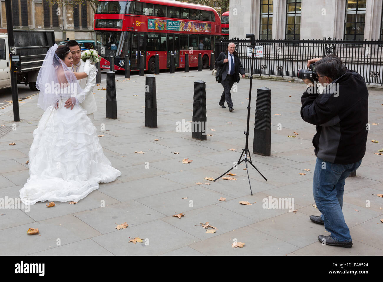 A Chinese couple have wedding photographs taken outside Westminster Abbey in London, England, UK - Stock Image